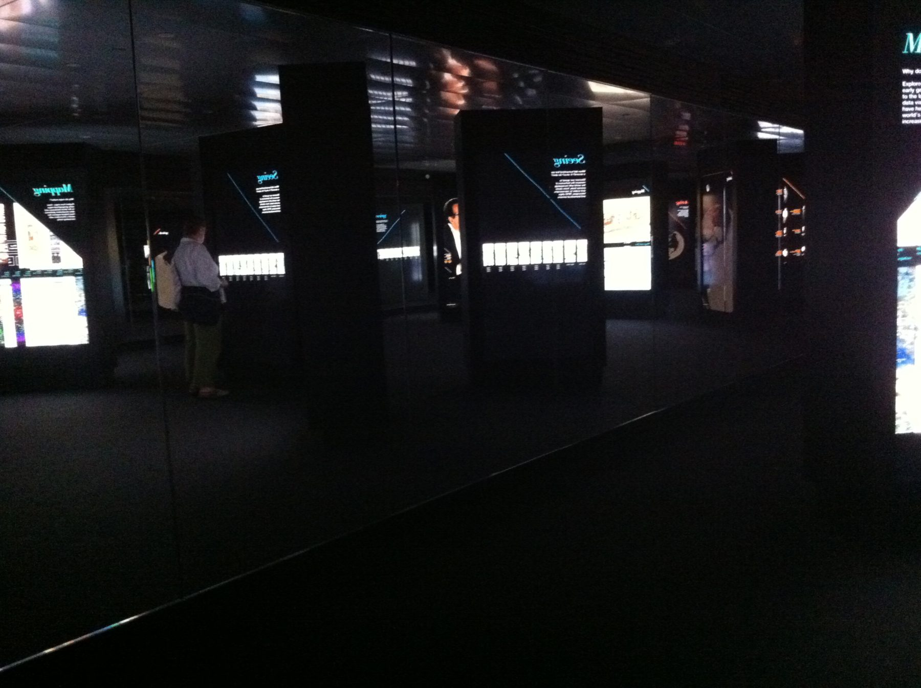 A dark room full of interactive screens.